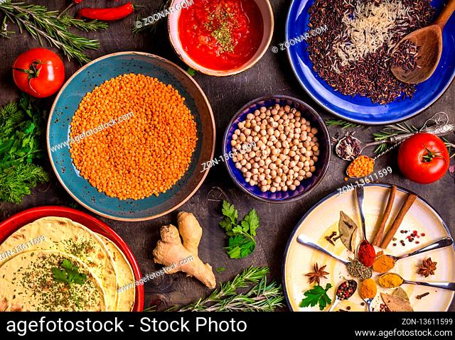Table served with traditional for asian or eastern cuisine food. Cereal grains, beans, spices on colorful plates. Lentil, basmati and wild rice mix, chick-pea