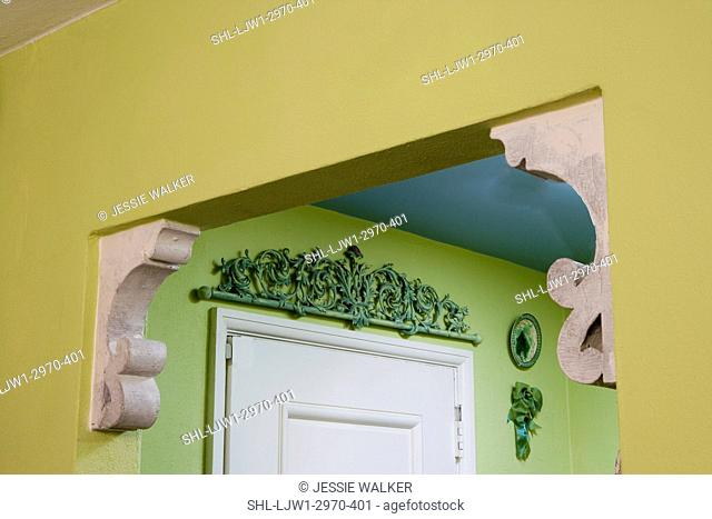 ARCHITECTURAL TRIM: Inventive reuse of corbels in doorway as accents, metal curlicue salvage piece hangs above door, colorful lime green and blue