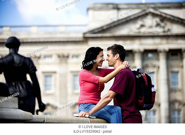 A young couple in front of Buckingham Palace, looking at each other