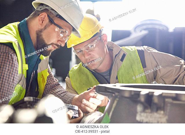 Steelworkers examining steel part in steel mill