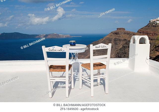 Postcard scene of two lonely chairs on terrace with table ready for tourists in Santorini Greece in Greek Islands