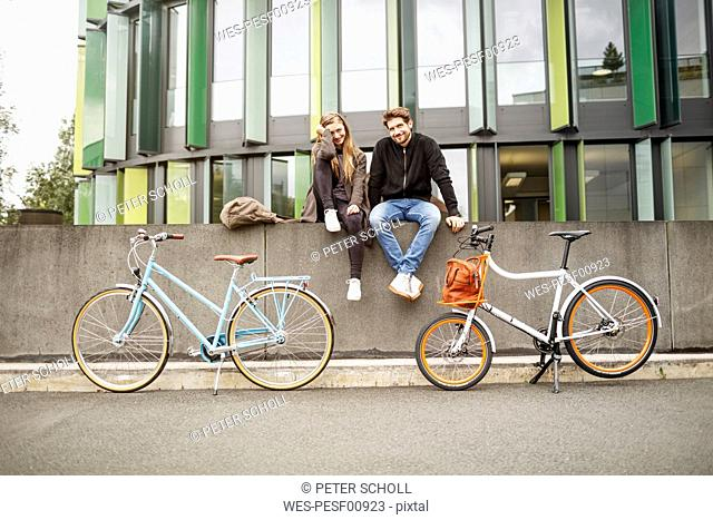 Happy couple with bicycles sitting on a wall