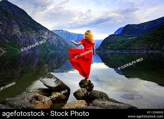 Blonde girl in a red dress moved by the wind standing on a rock in front of a lake, Eidfjord, Hordaland, Norway