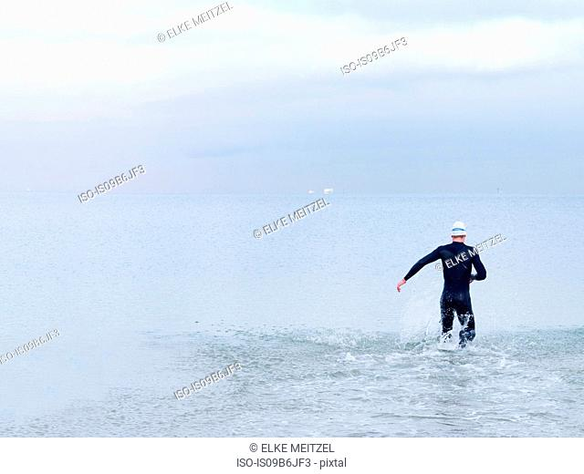 Rear view of man in wet suit and swimming cap in sea, Melbourne, Victoria, Australia, Oceania