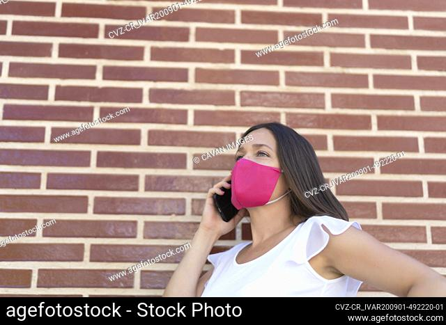 beautiful woman with pink mask talking on her smartphone