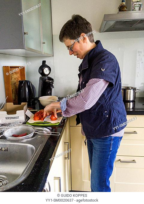 Tilburg, Netherlands. Mid adult caucasian woman, having multiple sclerosis or MS for over a decade, successfully slows down the process by eating very healthy...