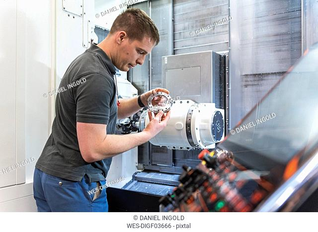 Man examining workpiece at machine in factory
