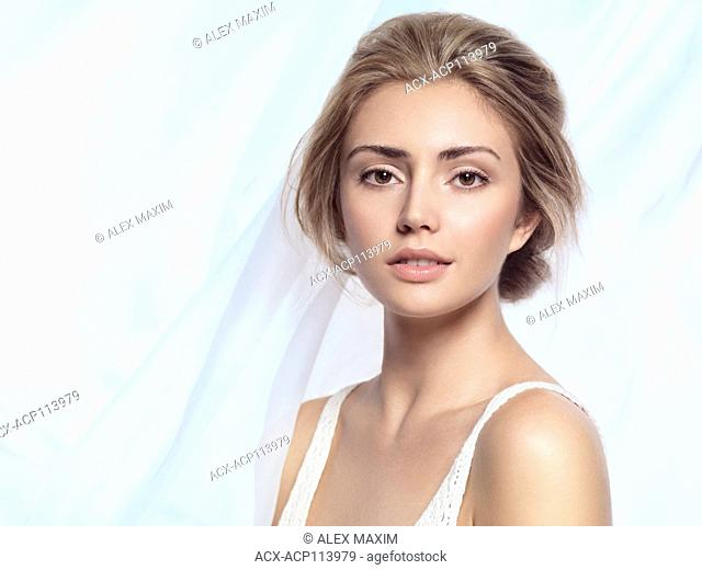 Young beautiful woman face beauty portrait with clean natural look on light blue flowy fabric background