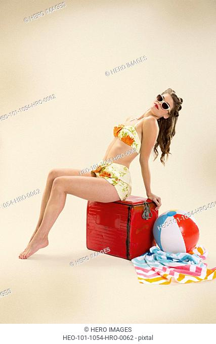 Full length of pin-up girl with beach equipment