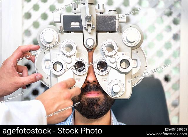 Optometrist doing sight testing for male patient In clinic. Male ophthalmologist examining patient man with optometrist trial frame