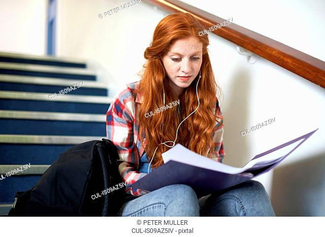 Young female college student sitting on stairway reading file