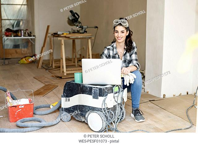 Young woman renovating her new flat, using laptop