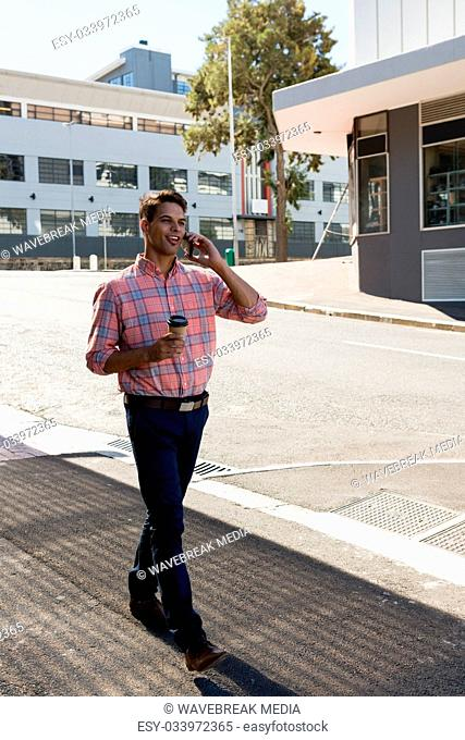 Young man having drink while talking on mobile phone