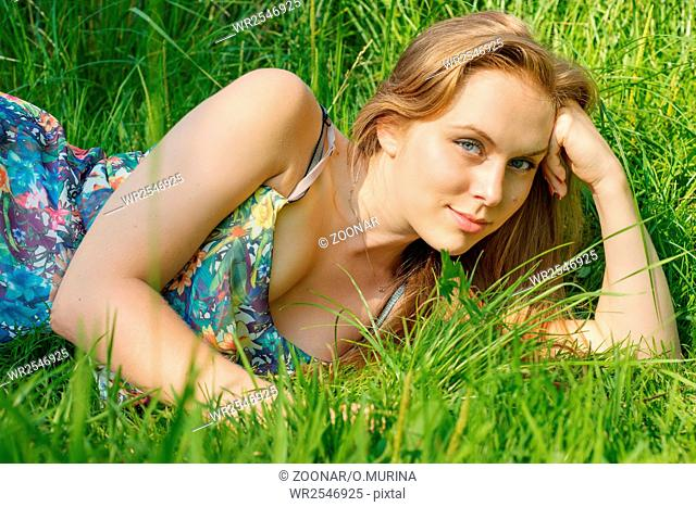 Young woman with long hair lying on the grass in summer