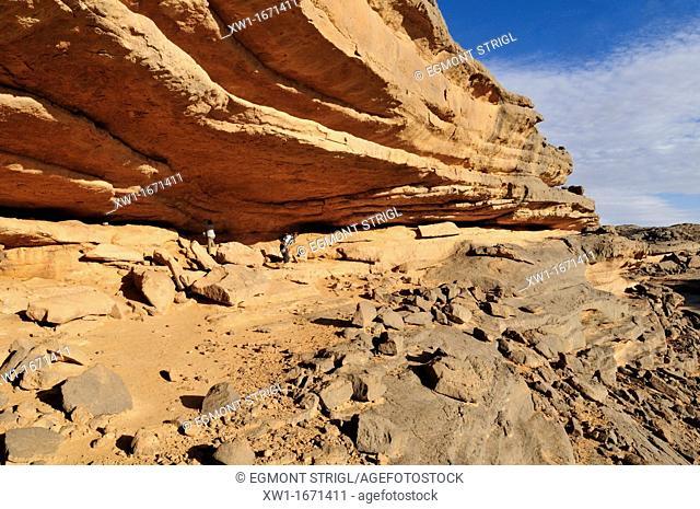 tourists in a Abri with neolithic rockart at Tin Meskis, Immidir, Algeria, Sahara, North Africa