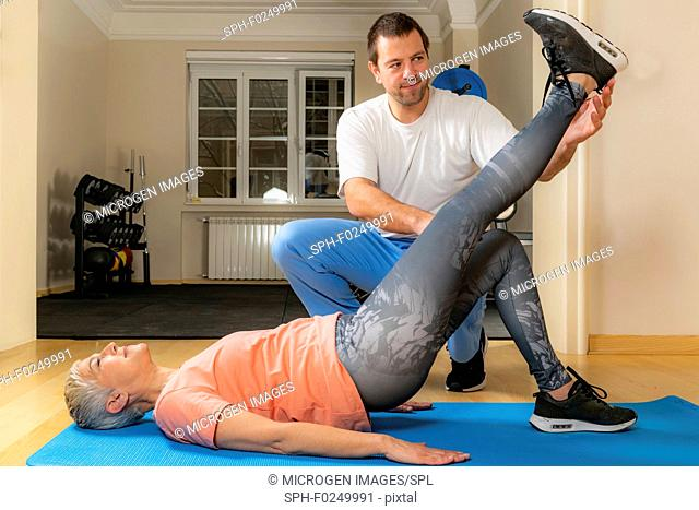 Physical therapist stretching senior woman