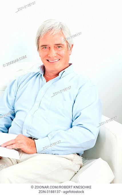 Älterer Mann liest entspannt ein Buch im Wohnzimmer