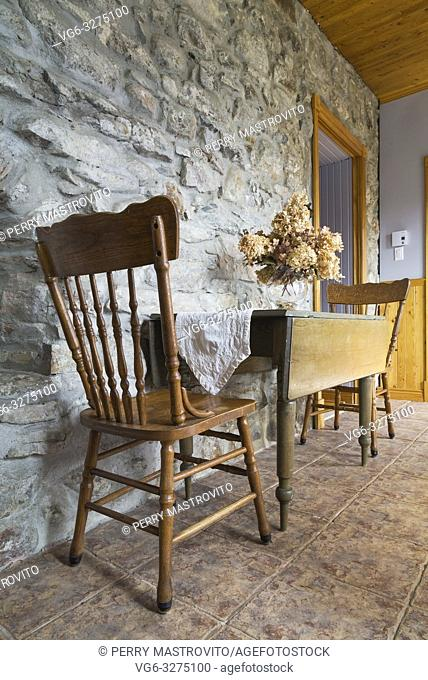 Antique wooden dining table and chairs in entryway with fieldstone wall and terracotta ceramic tile floor inside an old 1820 cottage style fieldstone house
