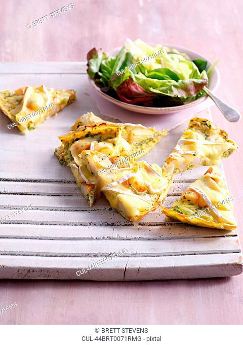 Tray of sliced quiche with salad