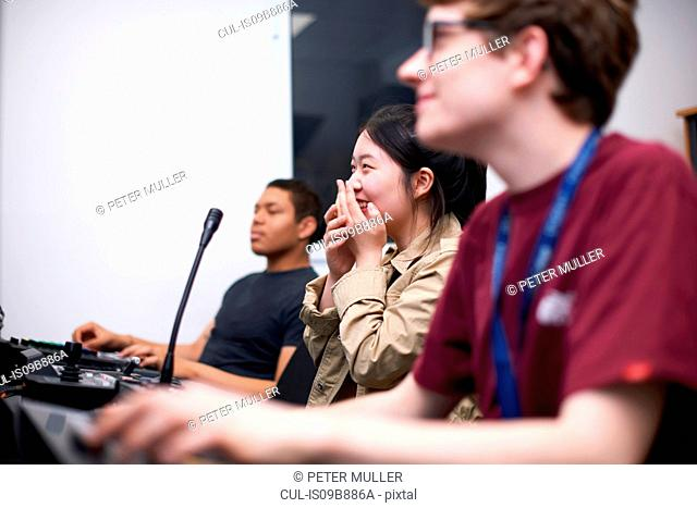 Young male and female college students at mixing desk in TV studio