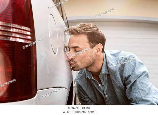 Man kissing his clean car