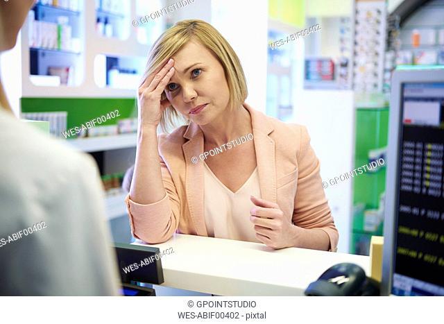 Pharmacist advising woman in pharmacy