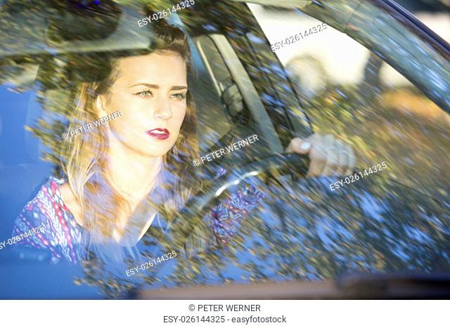 a brunette woman sitting in a car