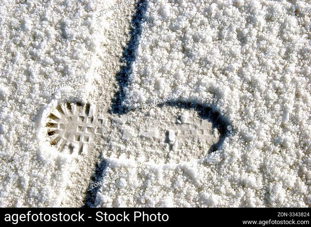 Human foot and bicycle wheel imprint in the snow