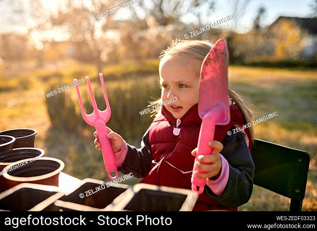 Portrait of girl holding gardening tools