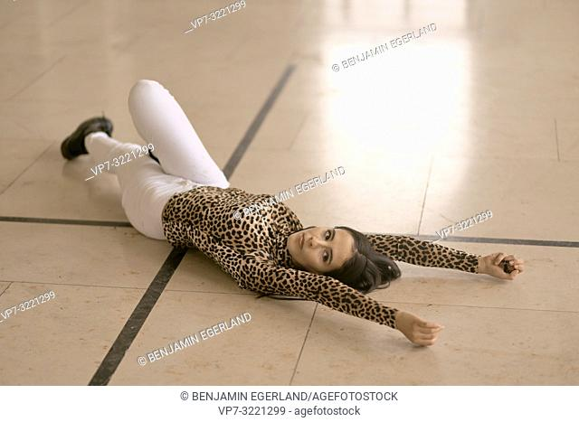 calm pensive woman laying on floor, wearing fashionable leopard print sweater, thoughtful mood, in Munich, Germany