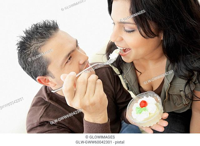 Close-up of a mid adult man feeding a young woman