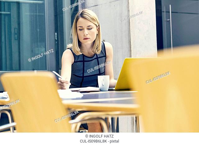 Young businesswoman writing at office desk