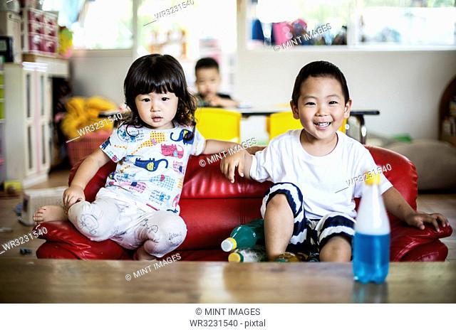 Smiling boy and girl sitting on red sofa in a Japanese preschool