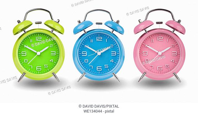 Three alarm clocks with the hands at 10 and 2 am or pm isolated on a white background