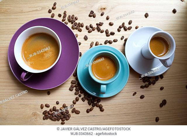 White porcelain cups, cyan and magenta with expresso coffee, on wooden board decorated with roasted coffee beans