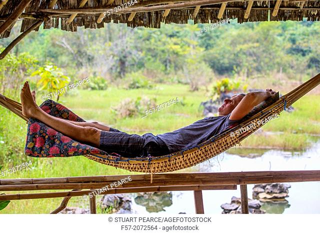Tourist relaxes in a bamboo hammock, Vang Vieng, Laos