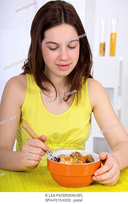MODEL RELEASED. Girl eating bowl of breakfast cereal