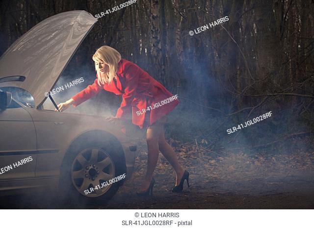 Woman looking under hood of car at night