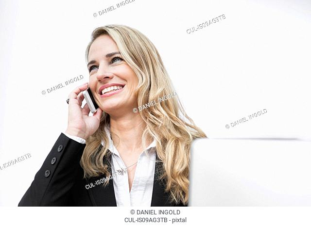 Mid adult businesswoman in office using cellphone
