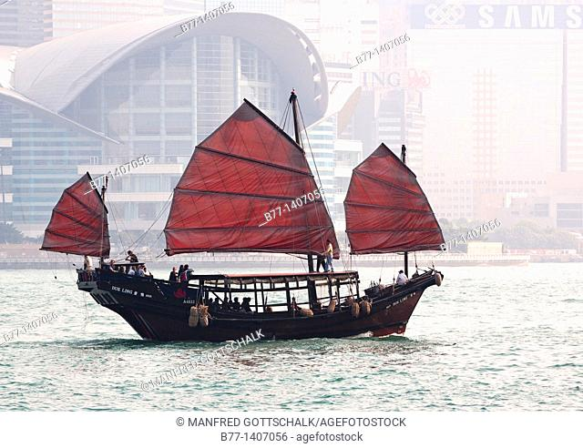 China, Hong Kong, Victoria Harbour, a sightseeing junk against the backdrop of the Hong Kong Convention and Exhibition Center