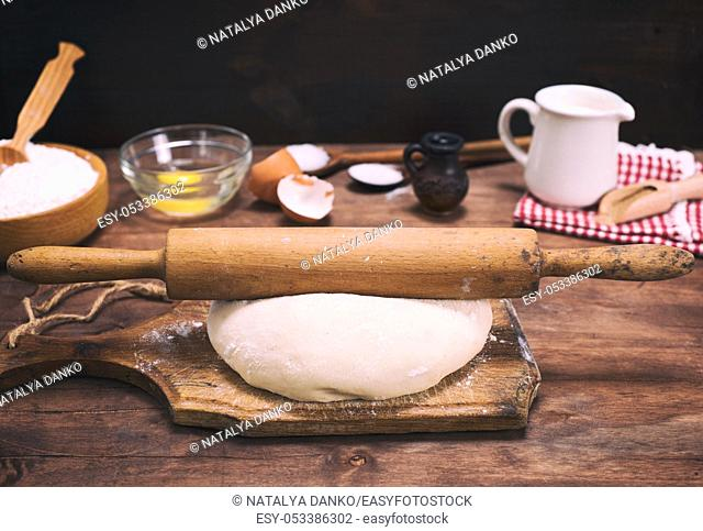 yeast dough from white flour and a wooden rolling pin on a brown board