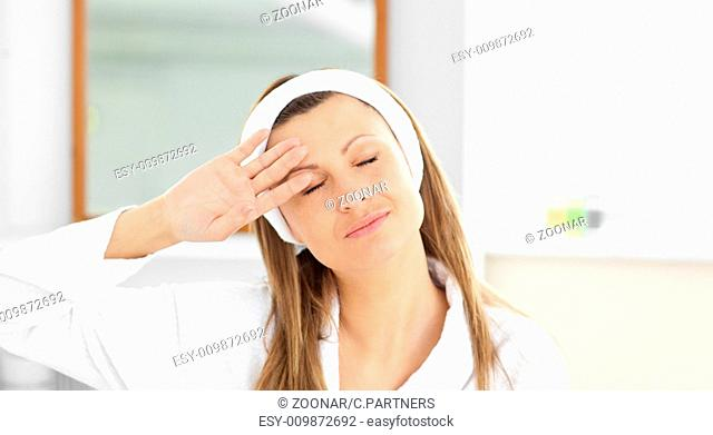 Positive woman putting cream on her face wearing a headband in the bathroom