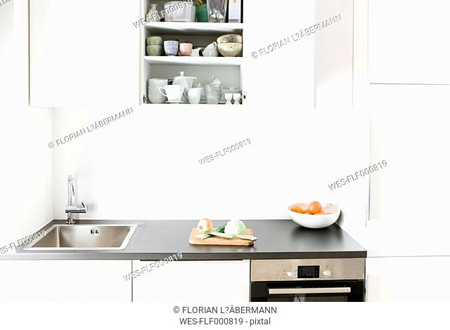 Modern kitchen, chopping board with vegetables, open cupboard