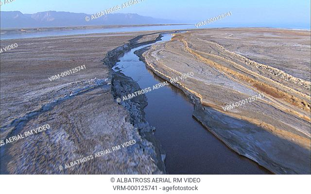 Aerial footage of the Dead Sea in the Judea Desert. A channel of water carrying irrigation water or a flooded wadi, carving out meander in flat hard