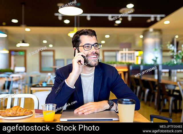 Portrait of happy businessman on the phone in a coffee shop