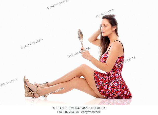 woman in summer dress looking at hand mirror - isolated on white