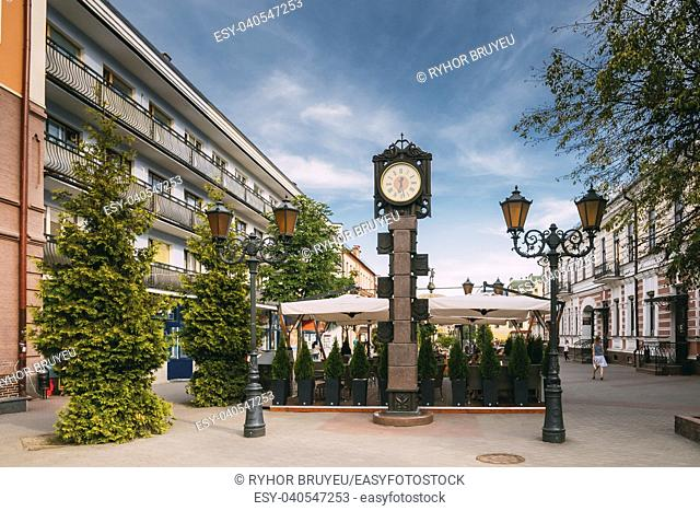 Brest, Belarus. Two-Sided Clock In Old-Fashioned Decoration With Arms Of City Of Different Times In Form Of A Six-Meter Bronze Monument On Pedestrian...