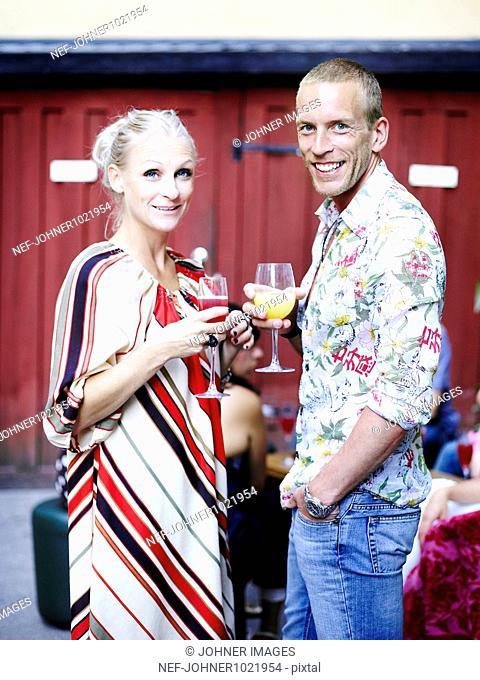 Sweden, Stockholm, portrait of young man and woman holding wine glasses