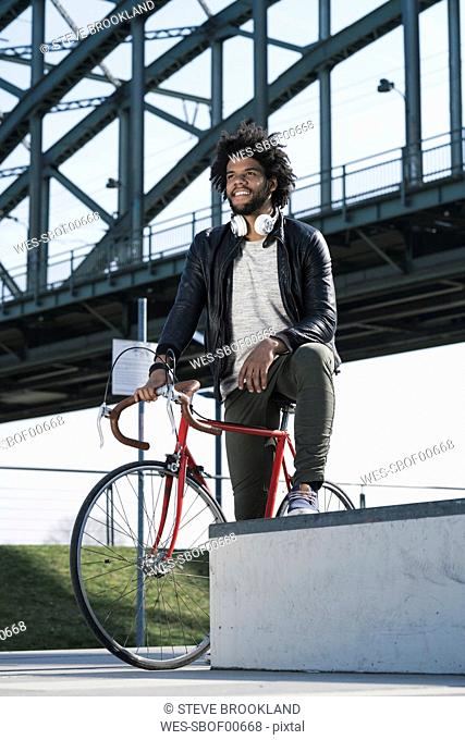 Man on bicycle in front of bridge