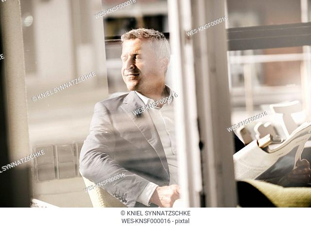 Businessman sitting in a cafe reading newspaper